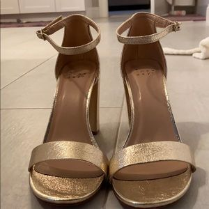 Gold heels with strap around the ankle